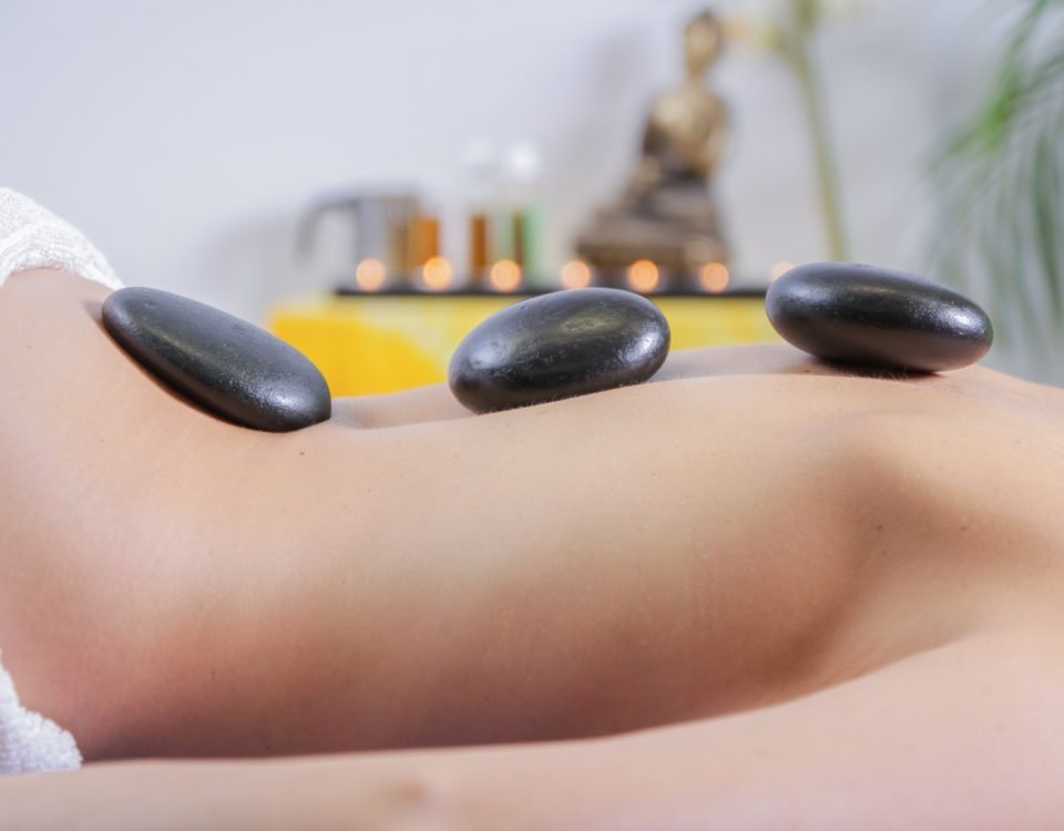 woman at spa with rocks on back